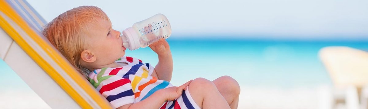 baby-drinking-from-bottle-on-the-beach-1440x430-1-1200x358.jpg